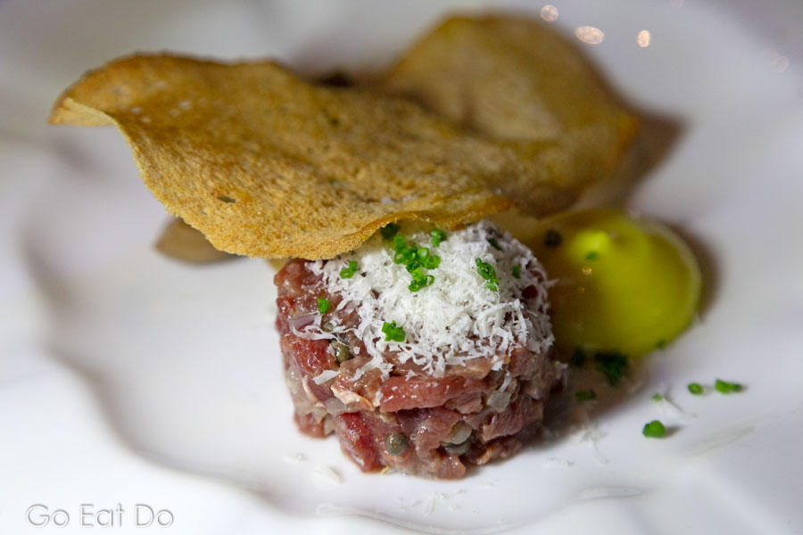 Steak tartare served with a thin slice of crisp bread.