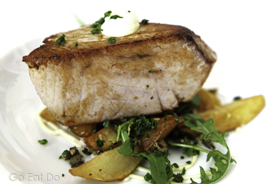 Tuna steak served with potato wedges, salad and a sauce of capers, green olives and lemon juice