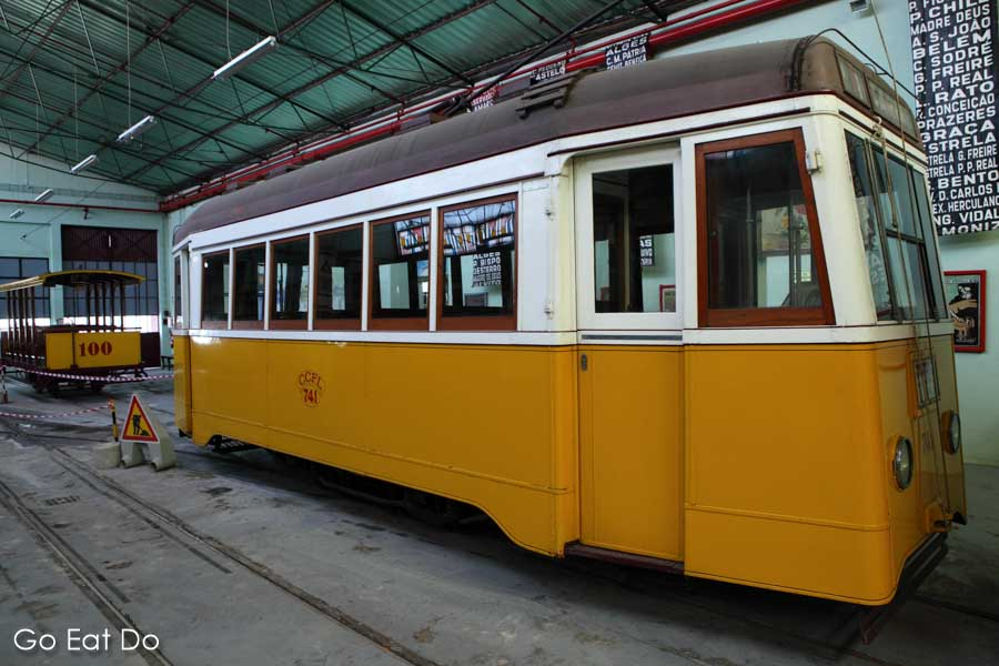 Historic trams displayed in the tram shed at the Museu da Carris transport museum in the Alcantara district of Lisbon, Portugal
