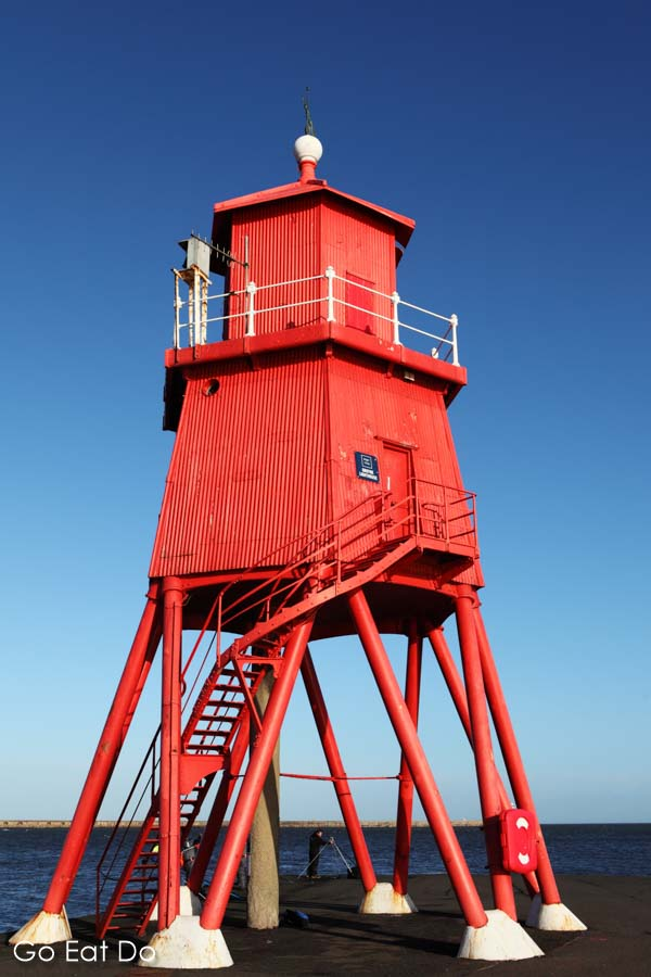 The red Herd Groyne lighthouse seen against a bright blue sky in South Shields, England