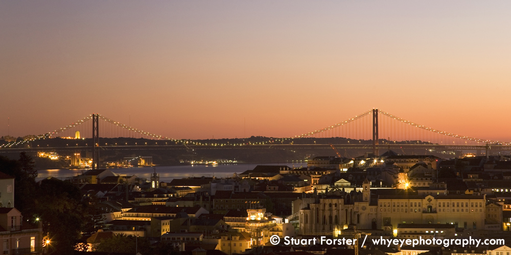 A golden dusk over the April 25 Suspension Bridge in Lisbon, Portugal
