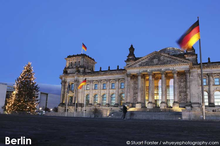 Christmas tree stands by the Reichstag Building, seen at the blue hour, in Berlin, Germany
