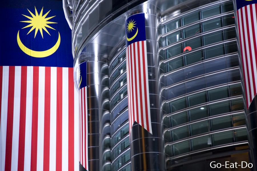 Malaysian national flag hangs outside of Petronas Towers at night in Kuala Lumpur, Malaysia.