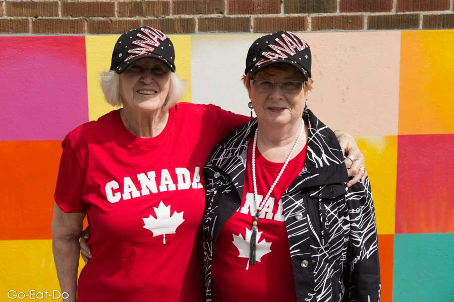 Women in Canada T-shirts and hats at the Lilac Festival in Calgary, Alberta, Canada