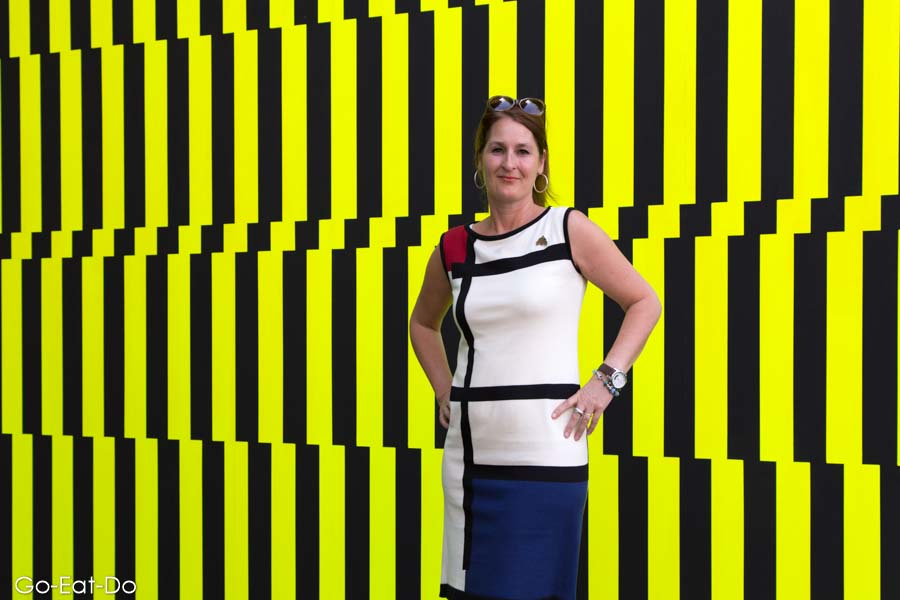 Woman in a De Stijl-influenced dress at the 100 Years After De Stijl outdoor art exhibition in Leiden, the Netherlands