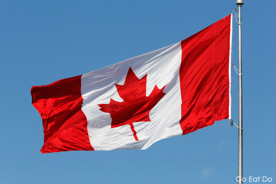 The Canadian flag and a clear blue sky.