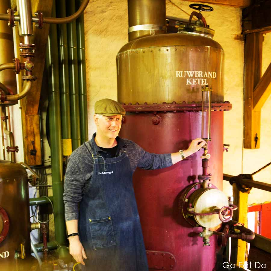 Pieter by a copper kettle at the Eisvogel distillery at Arcen in Limburg, the Netherlands