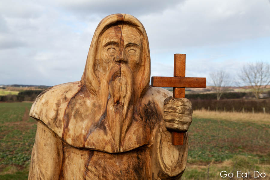 A carved wooden figure depicts St Cuthbert on St Cuthbert's Way. The cross pretty much marks the spot where we paused to eat a flask of soup.