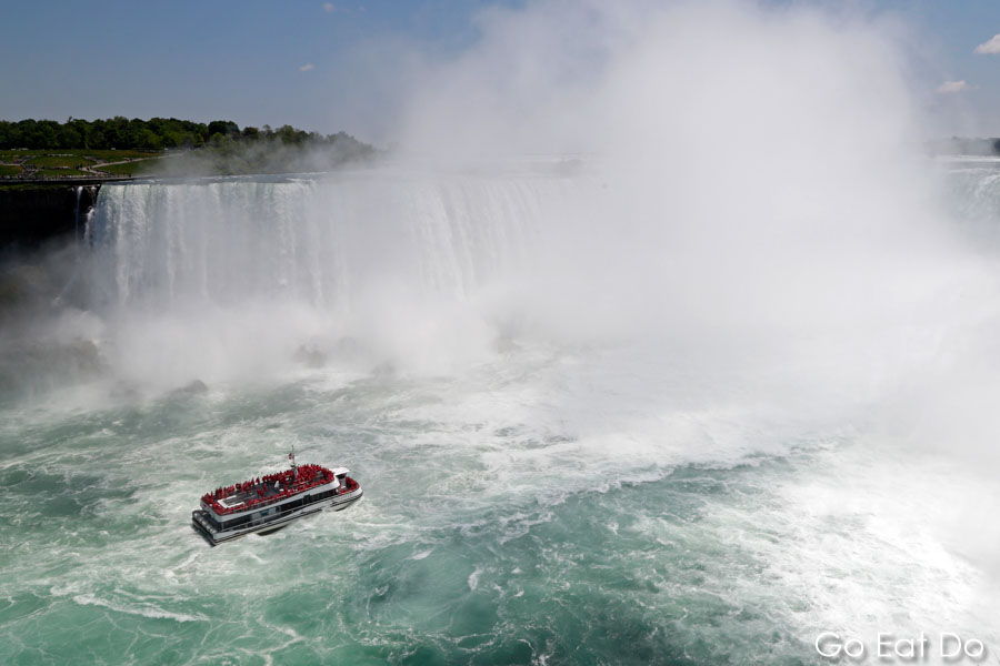 Hornblower Niagara Cruises sail into spray from the Horseshoe Falls at Niagara Falls on the border of New York State and Ontario