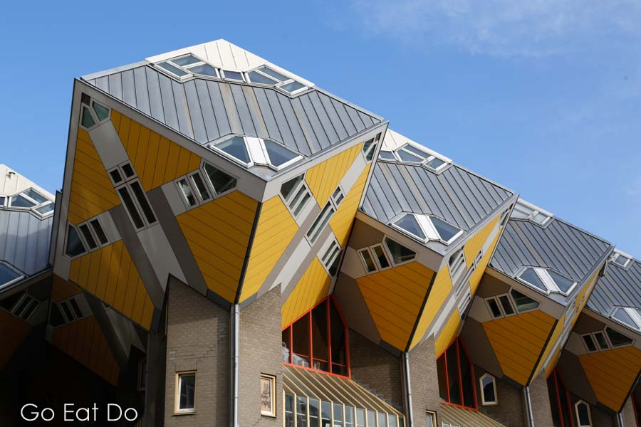 Yellow Cube Houses, designed by Piet Blom, under a blue sky on a sunny day in Rotterdam, the Netherlands