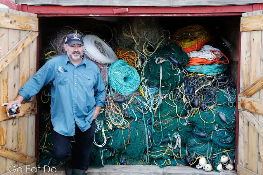 A fisherman shows off a shed packed with nets.