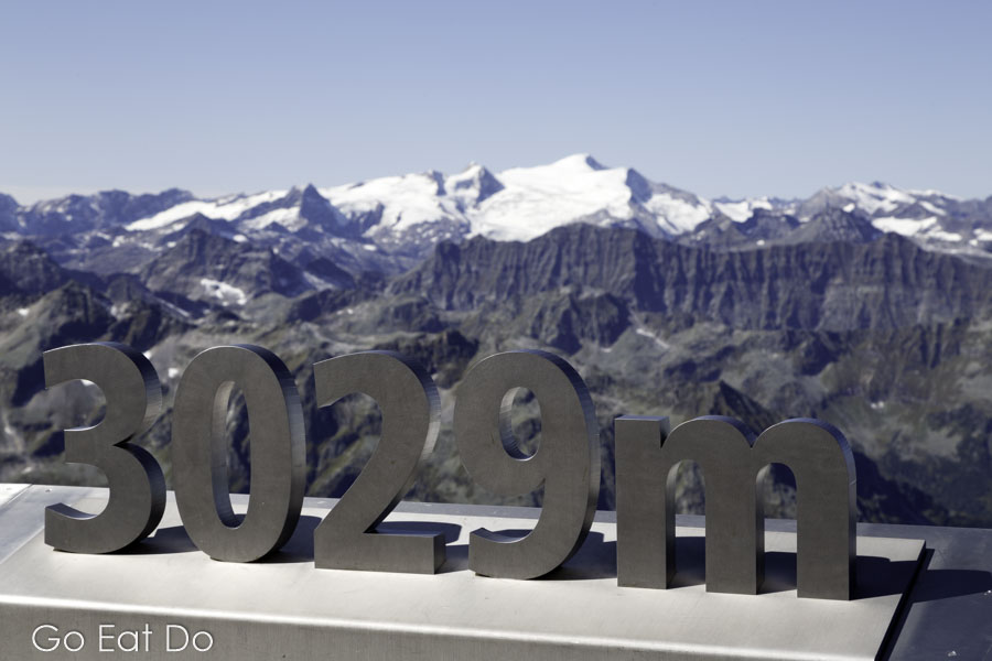 Snow-capped mountains beyond the sign for the 3,029m altitude at the Top of Salzburg observation platform in Salzburgerland, Austria