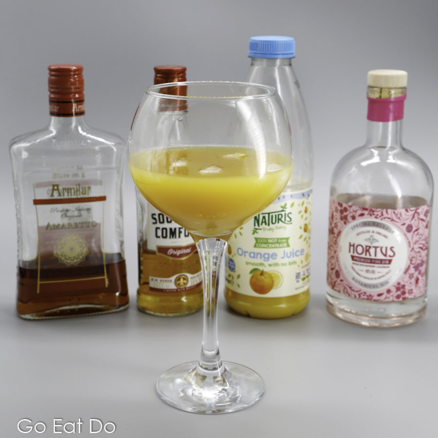 An Alabama Slammer along with the ingredients used to mix the classic cocktail menu
