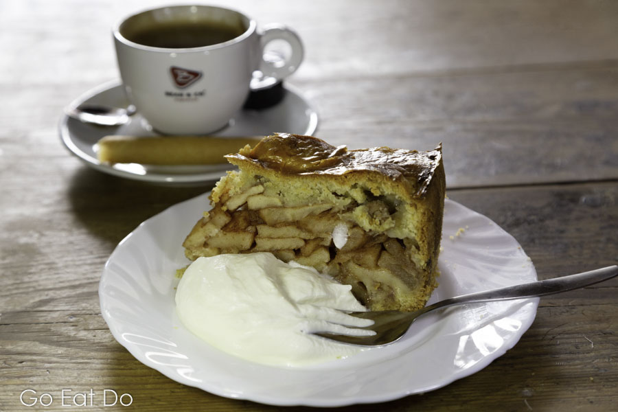 Traditional Dutch dish of appeltaart (apple pie) served with whipped cream and a coffee