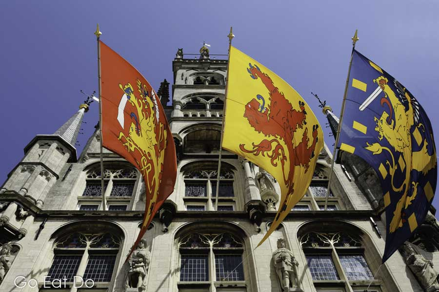 Flags fly from the Gothic town hall (stadhuis) of Gouda on a sunny day in the Netherlands