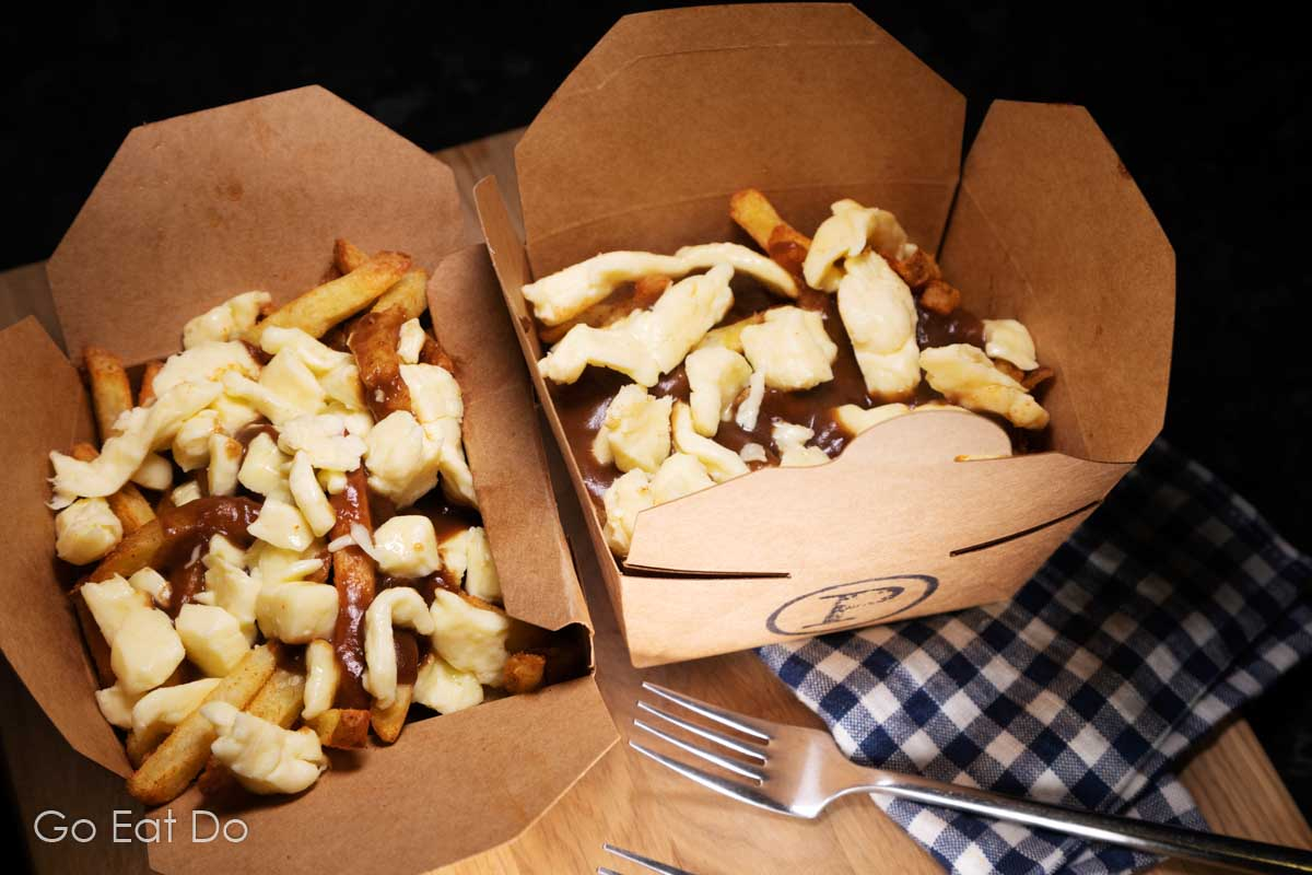 Two boxes of poutine made at home in boxes from The Poutinerie.