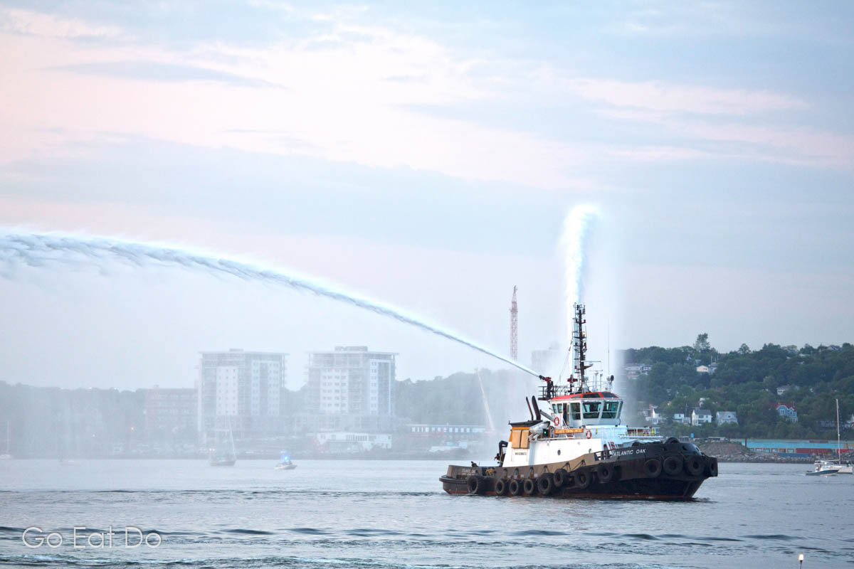 The Atlantic Oak tug boat shoots hoses into the air during the parade of sail as the Queen Mary 2 departs Halifax.