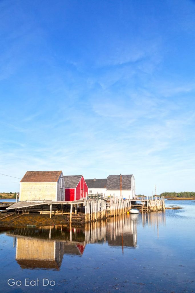 Fishing huts reflecting in the calm water of the Atlantic at Blue Rocks near Lunenburg in Nova Scotia.