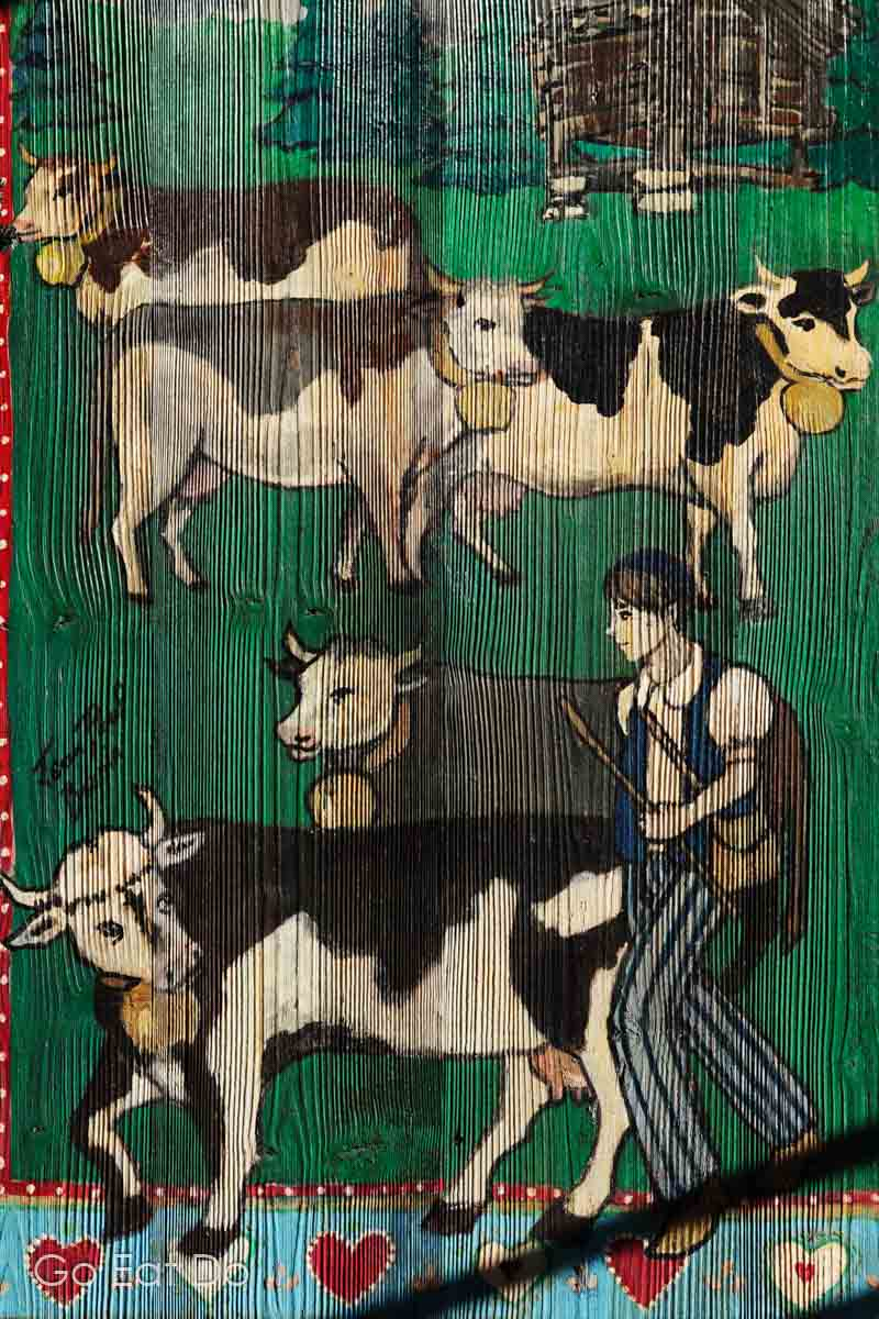 An Alpine scene painted on wood depicting cows and a cowherd in an Alpine meadow.