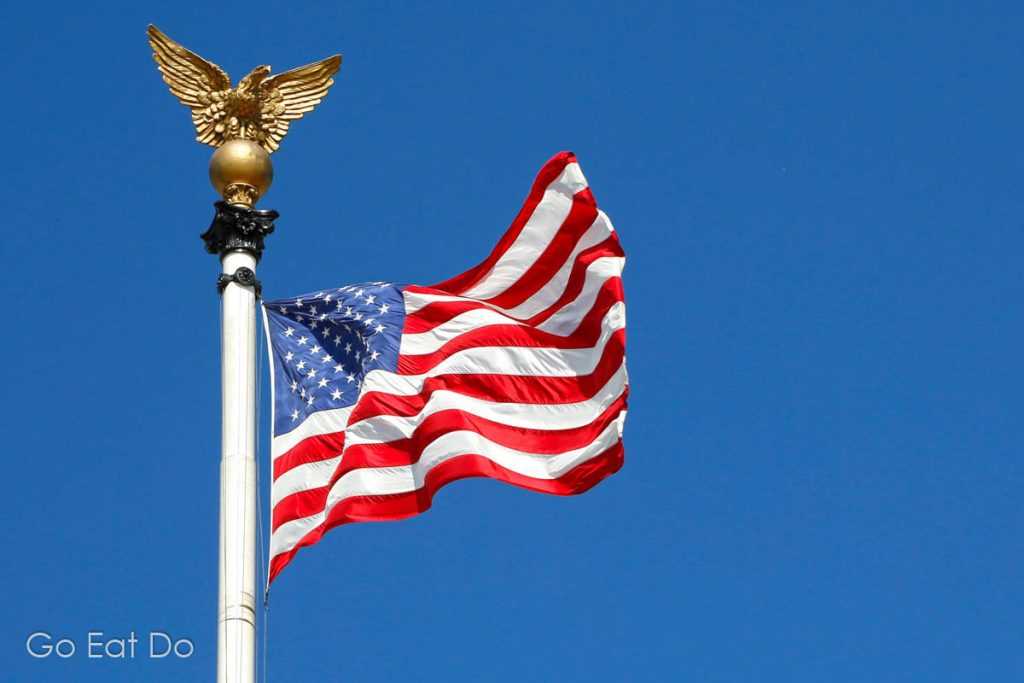 A golden eagle tops a flagpole from which the Stars and Stripes flies on a sunny day.