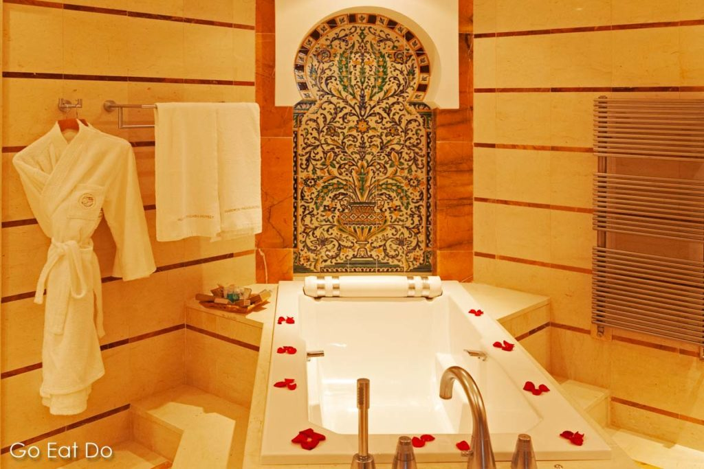 Bathrobe hangs by a bathtub strewn with rose petals in a luxury hotel offering thalassotherapy in Tunisia.