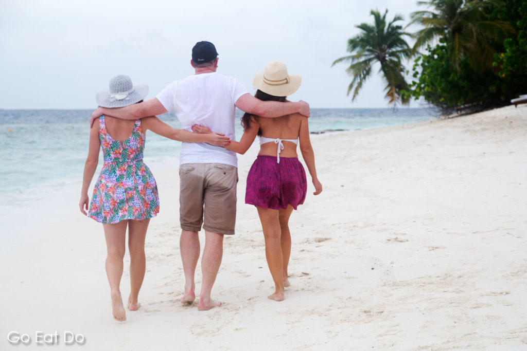 Man and two women walking along a beach on an island resort in the Maldives