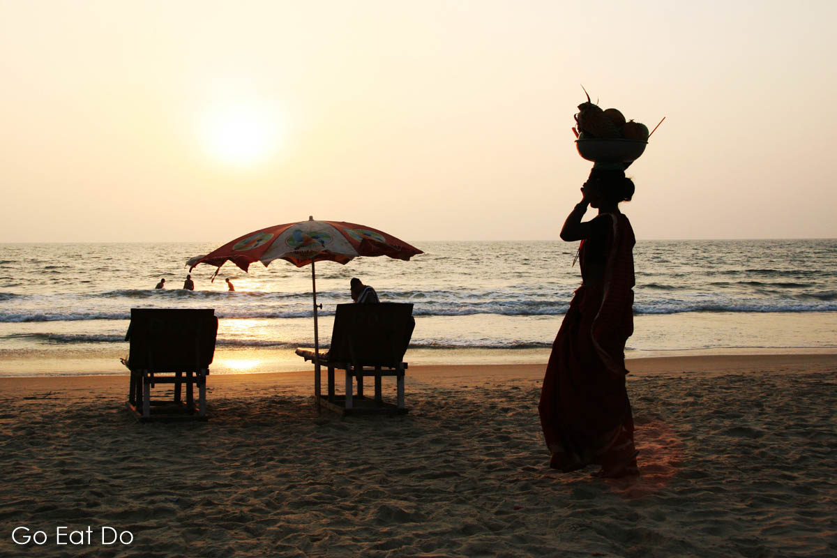 Indian woman walks along a beach washed by the Arabian Sea as the sun sets in Goa, India.