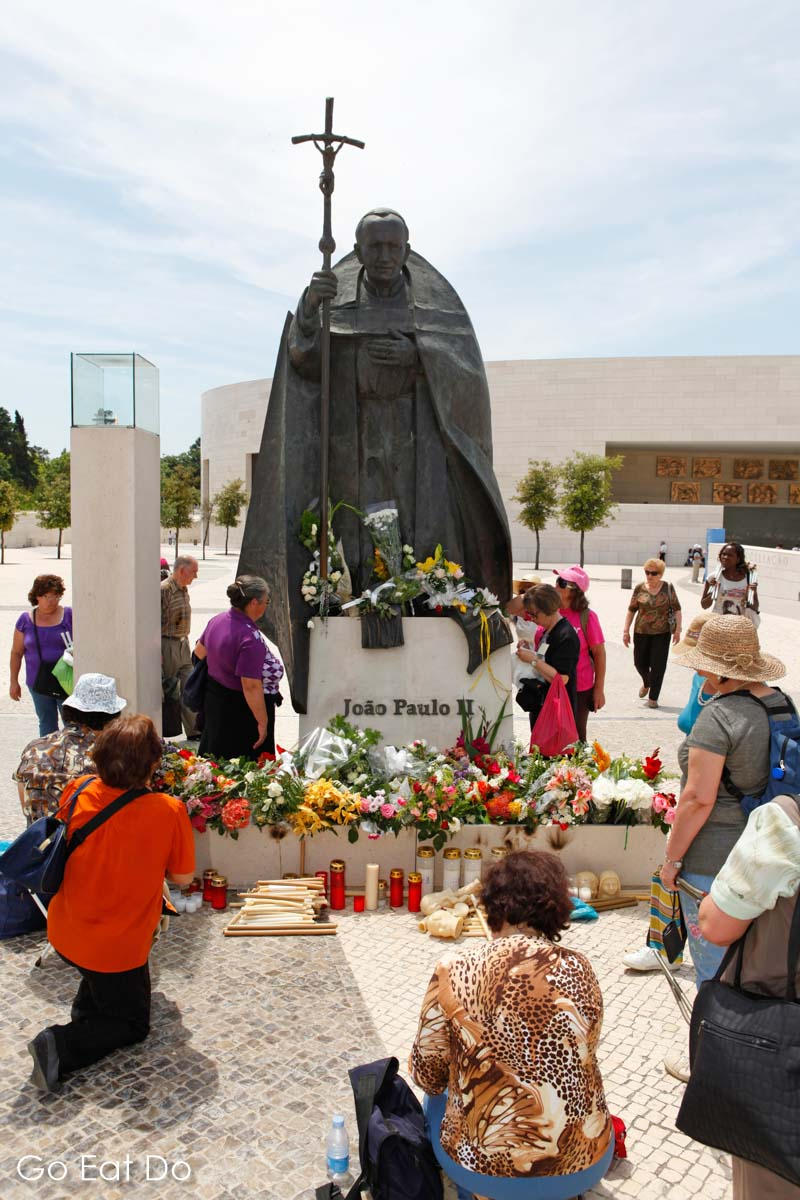 Christians pray by the statue of Pope John Paul II in Fatima, Portugal, on the Feast of Our Lady of the Blessed Sacrament on 13 May 2011.